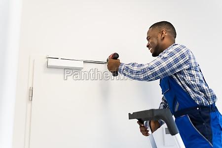 african man installing and fixing door