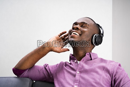 happy african american man enjoying music