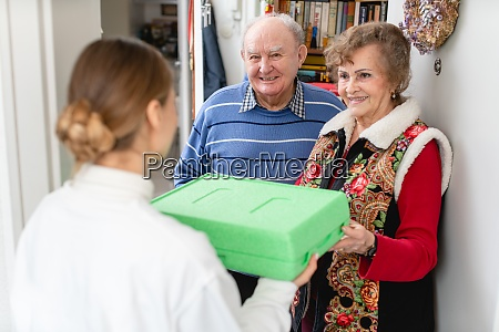 senior couple greeting volunteer delivering a