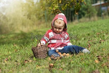 baby boy holding wicker basket is