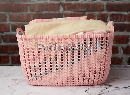 pink plastic basket with folded washed