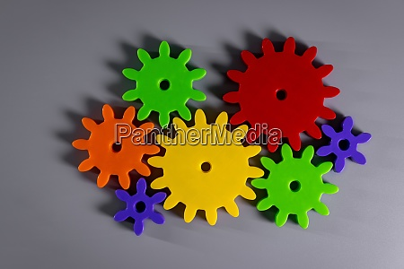colorful connected gears on gray background