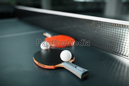 ping pong rackets and ball at