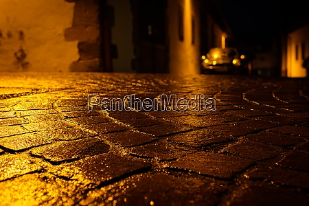 wet cobblestone road in night with