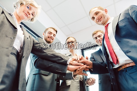 business team stacking hands looking at