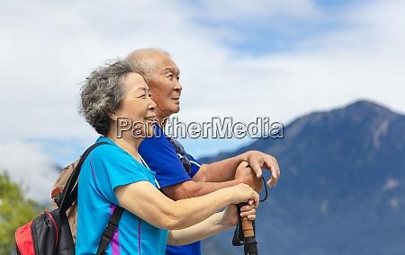 happy asian senior couple hiking in
