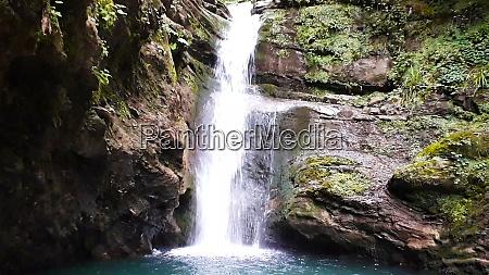 beautiful fresh waterfall among tall rocks