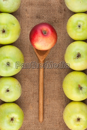 spoon with red apple lying on