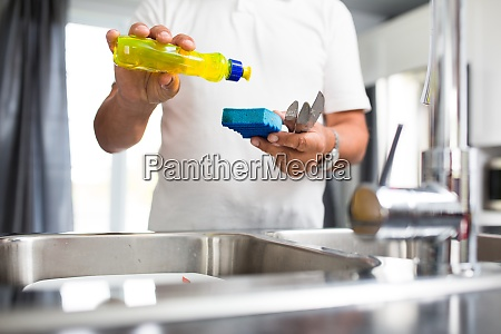 senior man washing dishes in his