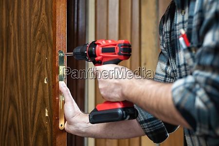carpenter at work repairs the door