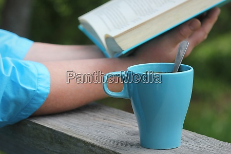 woman reading book outdoors coffe cup
