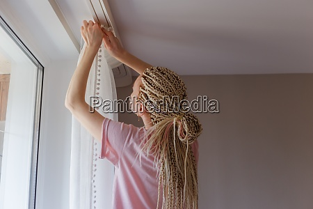 woman hanging up curtains at the