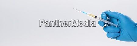 hand holding syringe with vaccine against