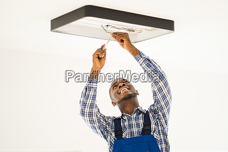 african maintenance electrician on ladder fixing