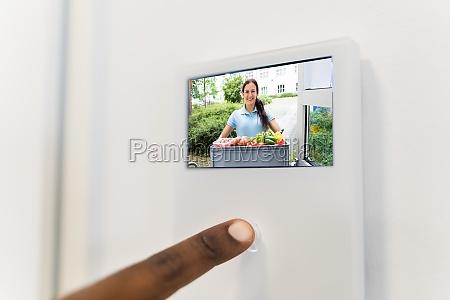 african man using video intercom system