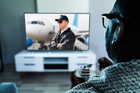 african man watching tv movie in