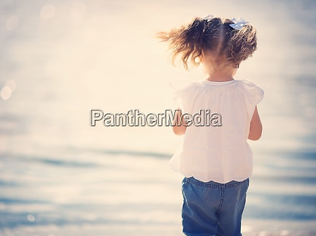 little girl sitting at the sea