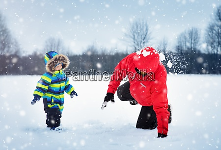 father with sons walking at snowfall