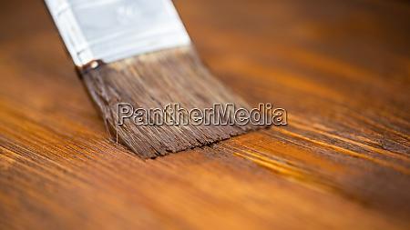 close up of paintbrush applying brown