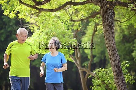 asian senior couple jogging in