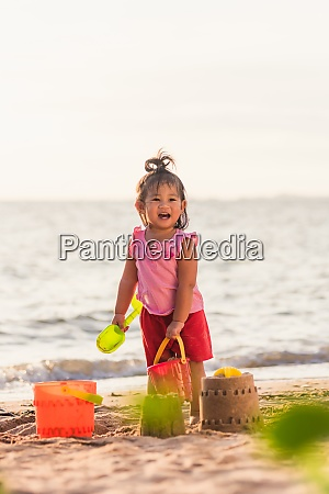 little girl playing sand with toy