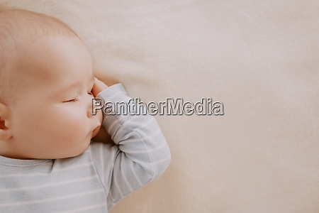 baby sleeping covered with soft white