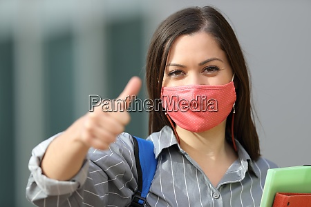 happy student wearing mask with thumbs