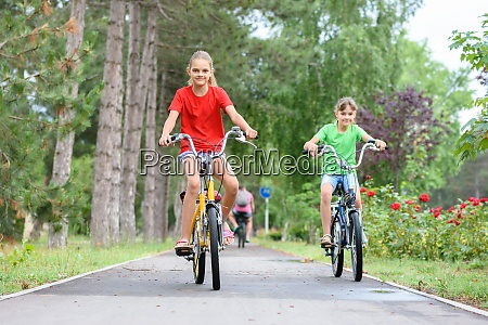 two girls ride a bike on