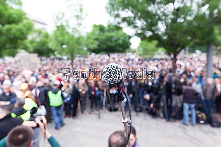 microphone in focus against blurred protest