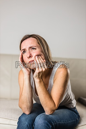 mid aged woman touching her cheekmouth