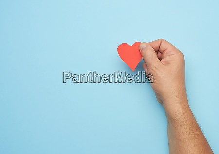 male hand holding red paper heart