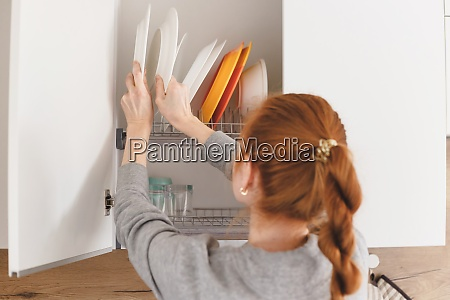 opening kitchen cabinet door woman putting
