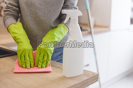 close up woman cleaning kitchen using