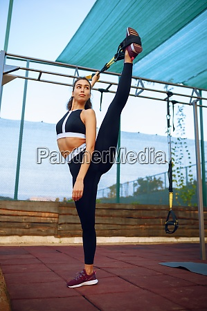 sportive woman doing stretching exercise outdoors