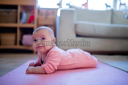 smiling baby girl lying down on