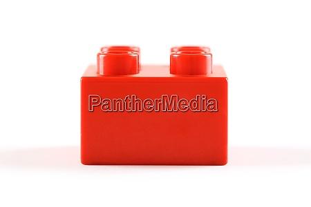 red plastic legoduplo block on white