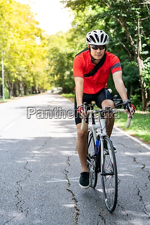 asian man cycle in countryside road