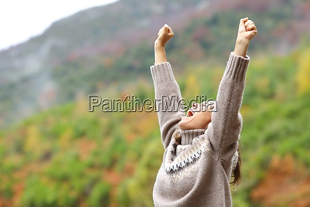 middle age excited woman raising arms