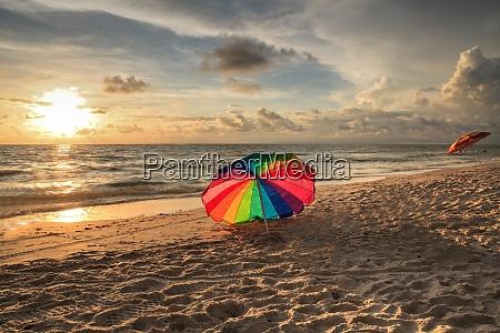 rainbow umbrella on white sand at