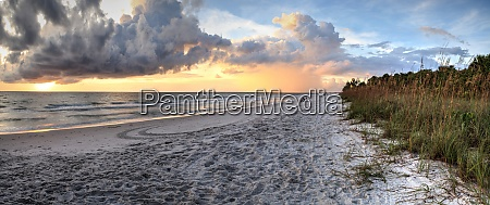 sunset over the white sand at