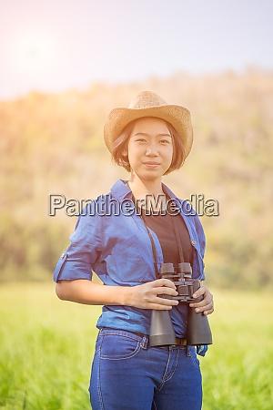 woman wear hat and hold binocular