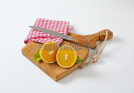 two fresh orange halves on cutting