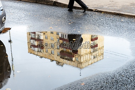 cityscape with puddle with reflection of