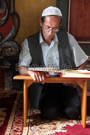 muslim man reading the koran in