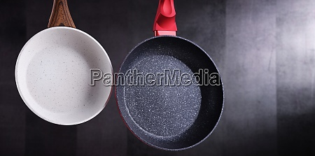two hanging stainless frying pans