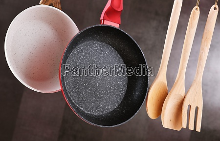 two hanging frying pans and kitchen