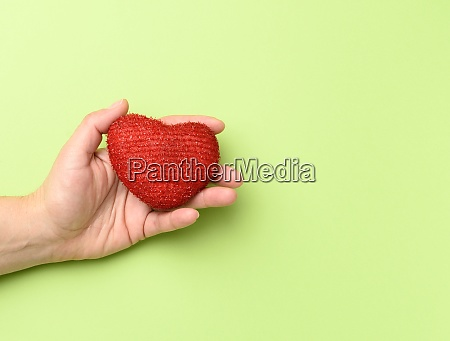 female hands holds red textile heart