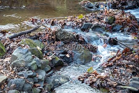 woodland stream flows around rocks fallen