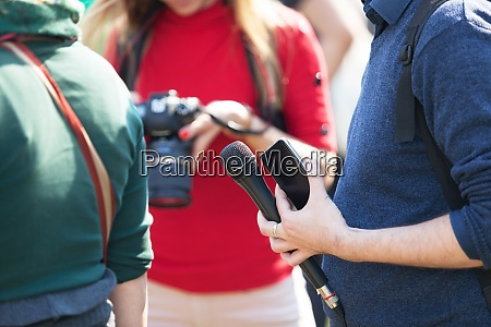reporter at media event holding microphone