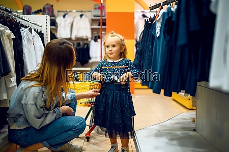 mother and little baby choosing dress